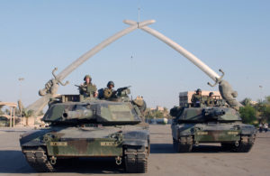 "US Army (USA) M1A1 Abrams MBT (Main Battle Tank), and personnel from A Company (CO), Task Force 1st Battalion, 35th Armor Regiment (1-35 Armor), 2nd Brigade Combat Team (BCT), 1st Armored Division (AD), pose for a photo under the ""Hands of Victory"" in Ceremony Square, Baghdad, Iraq during Operation IRAQI FREEDOM. The Hands of Victory monument built at the end of the Iran-Iraq war marks the entrance to a large parade ground in central Baghdad. The hand and arm are modeled after former dictator Saddam HusseinÕs own and surrounded with thousands of Iranian helmets taken from the battlefield. The swords made for the guns of dead Iraqi soldiers, melted and recast into the 24-ton blades."